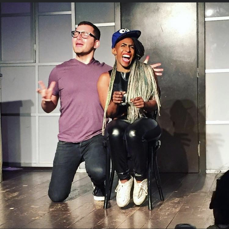 Black female comedian, Mirage Thrams, performing with white male comedian on stage