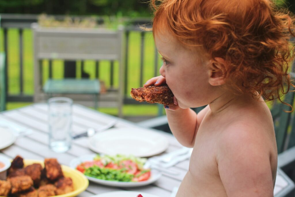 Child eating salmon cutlet outdoors