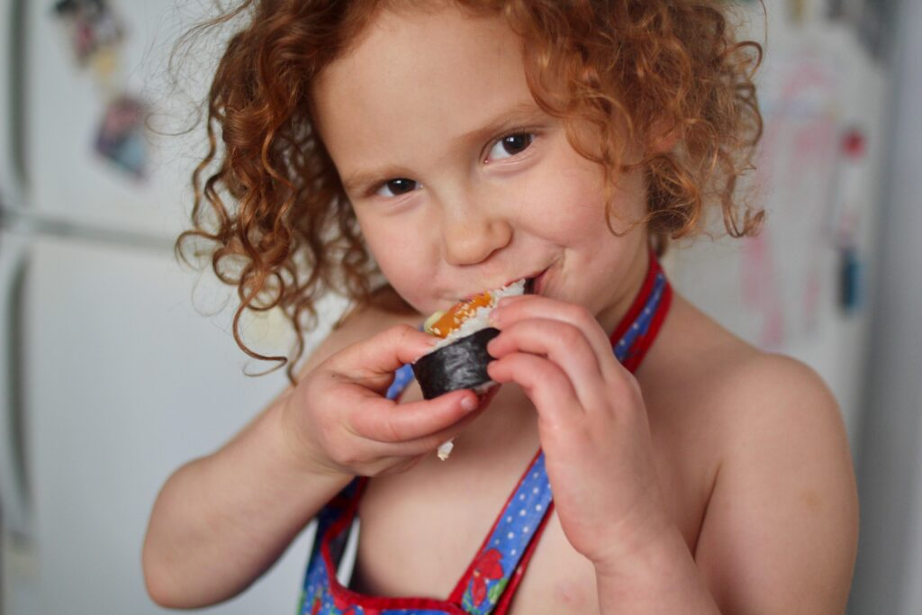 red head toddler eating japanese sushi roll