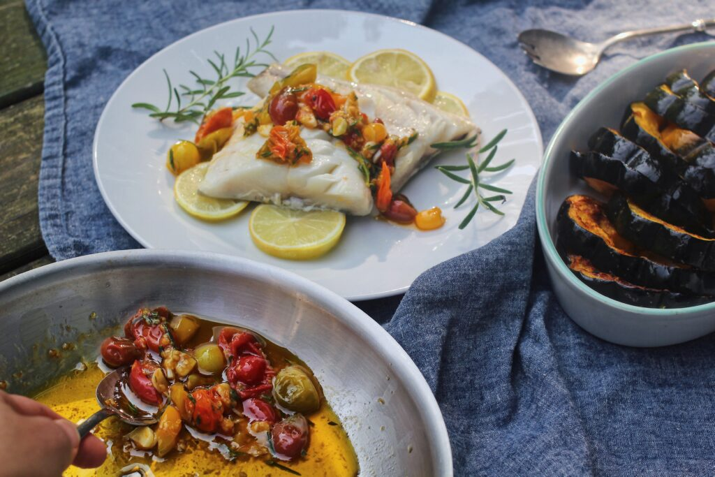 Scooping Lemon-Rosemary Braised Tomatoes onto Baked Black Cod